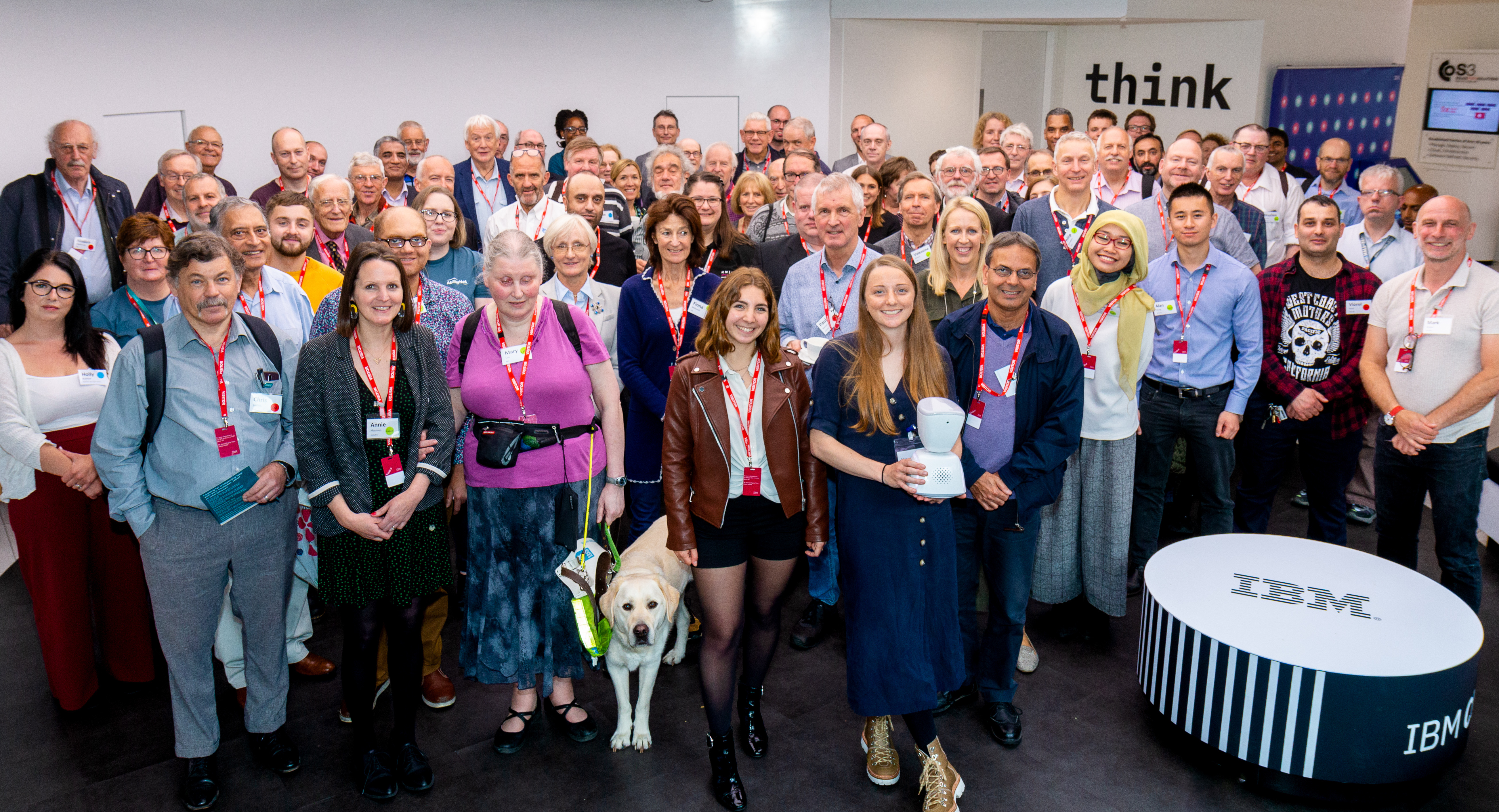 AbilityNet and RNIB volunteers standing together at the event, smiling facing the camera