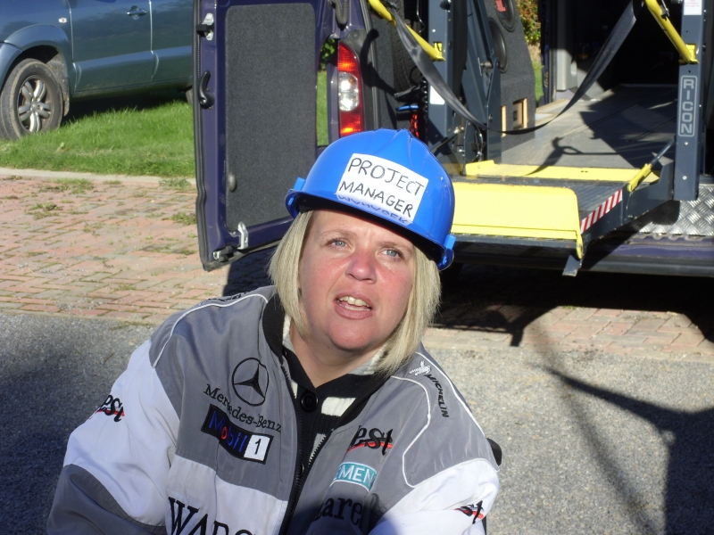 A photo of laura in front of a vehicle wearing safety gear with the label 'Project Manager' on her hard hat