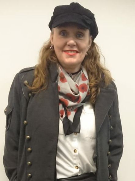A picture of Pamela Bateman Lee. She wears a cap and a scarf with poppies on it