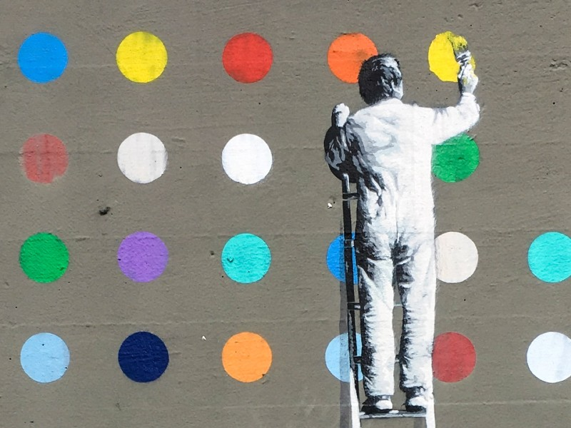 Image of man painting dots on a wall