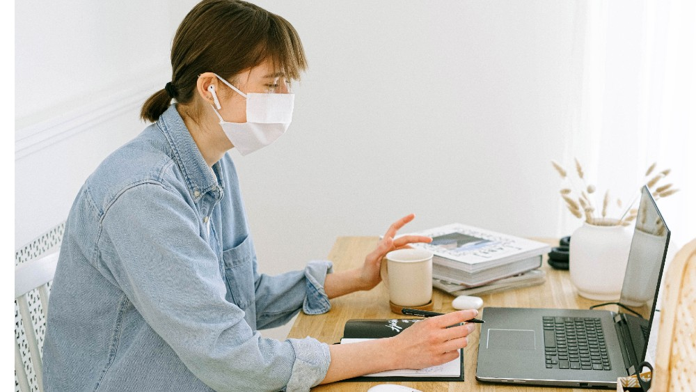 Person wearing face mask while working on laptop