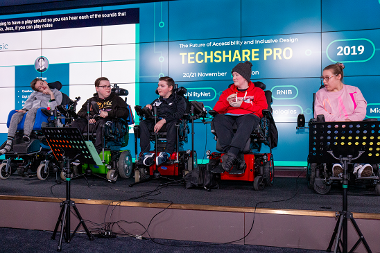 Colour photo of students on stage in wheelchairs using Digit Music technology