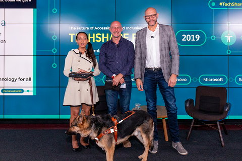Colour photo of Mark Walker, Haben Girma, her guide dog and Paul Walsh