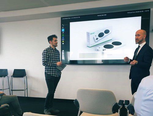 Chris Hughes presenting with Hector Minto of Microsoft in front of a screen showing the XBox adaptive controller