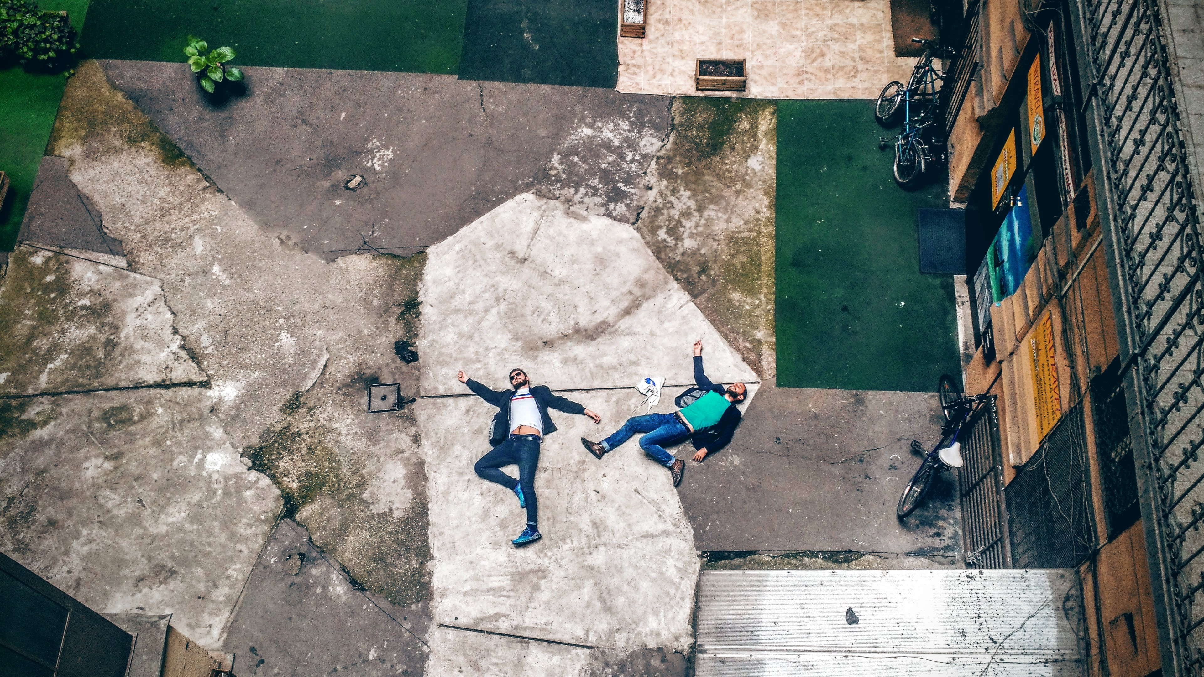 Two men lying on a slab of broken concrete, looking exhausted. Overhead shot as if they have fallen.