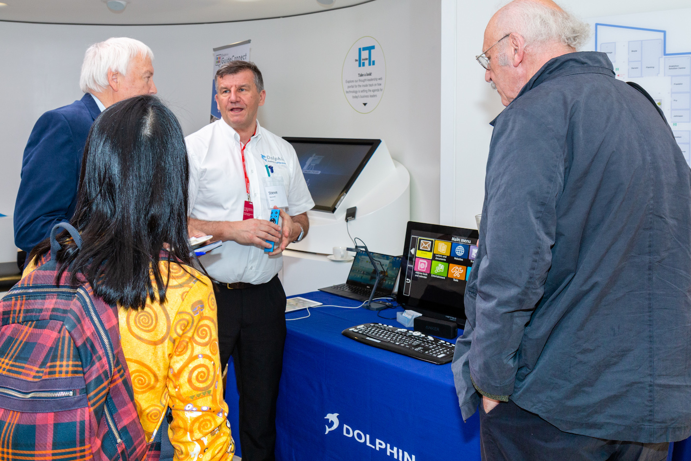A representative from Dophin demonstrating their assistive tech to event attendees
