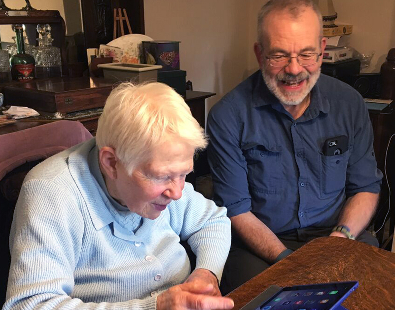An AbilityNet volunteer helping a lady in her home to use a tablet device