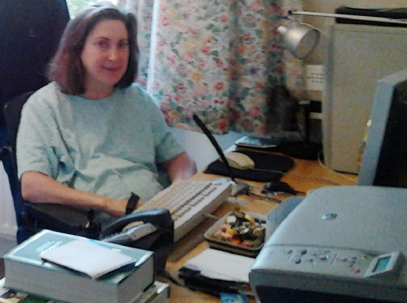 Belinda at her desk with assistive technology and her computer in front of her
