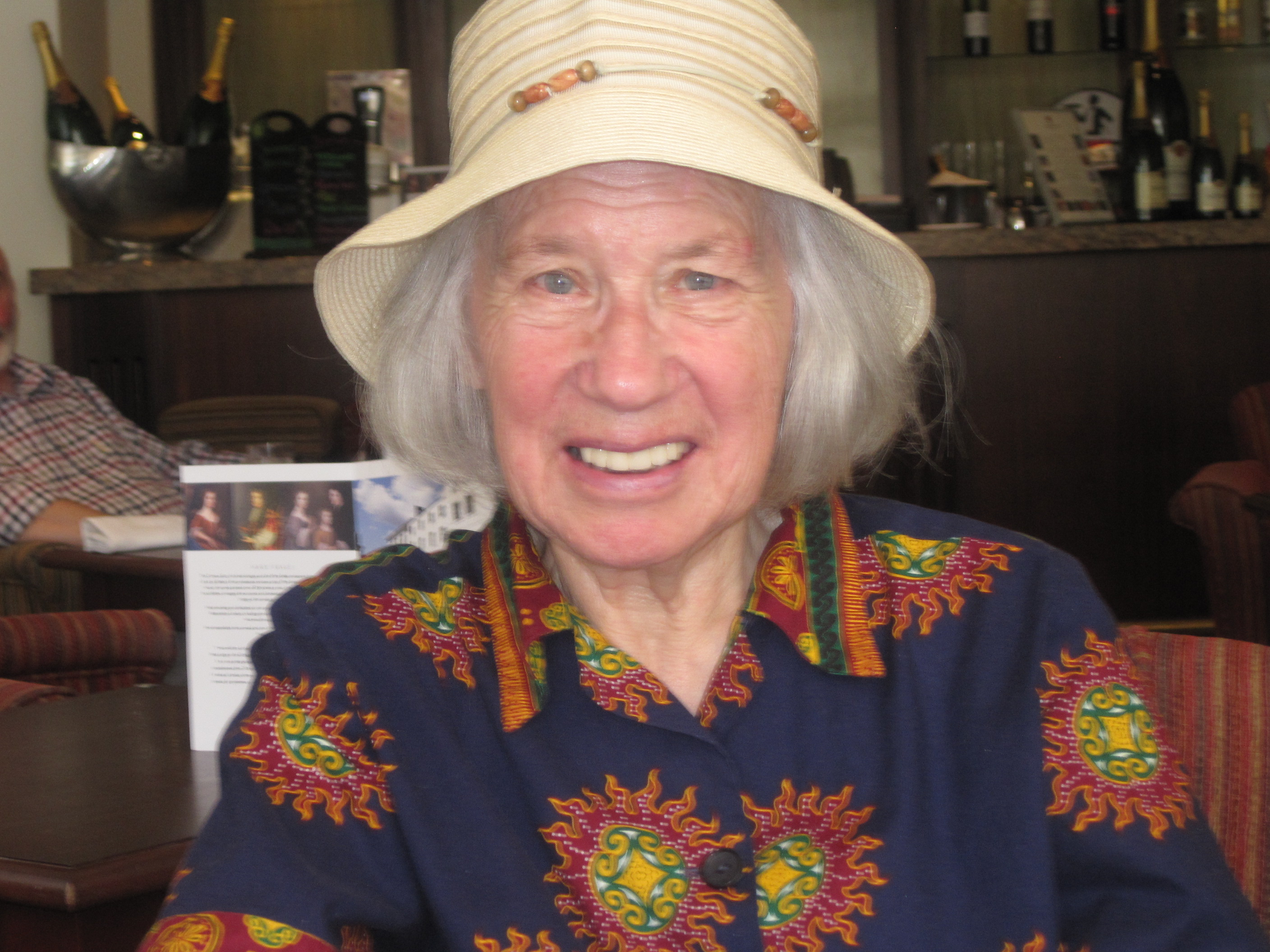 A picture of Iva, 85, she wears a sun hat and a bright shirt