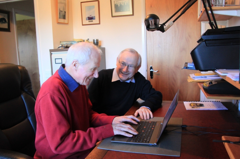 Malcolm helping Jim use his laptop in his home at his desk
