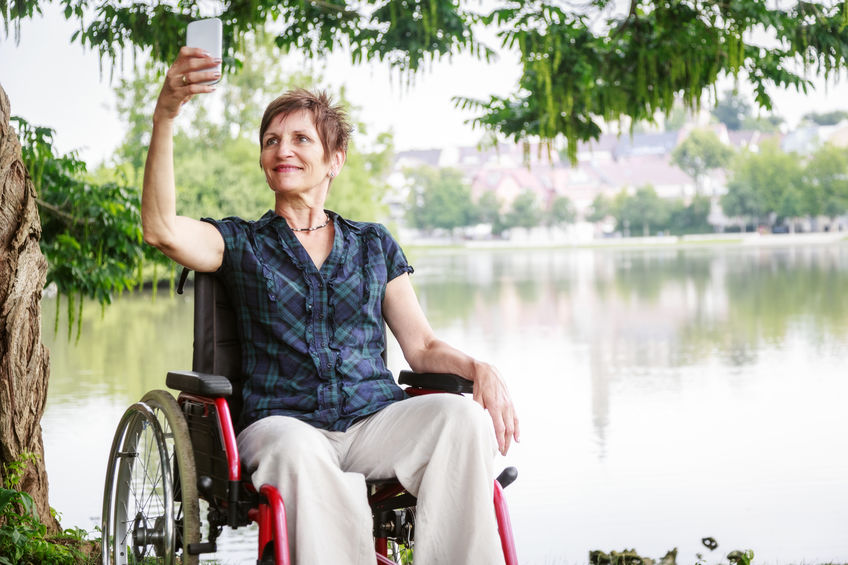 Older woman sitting in a wheelchair taking a selfie against a backdrop of a lake