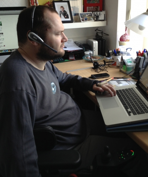 Sean at his laptop wearing a headset