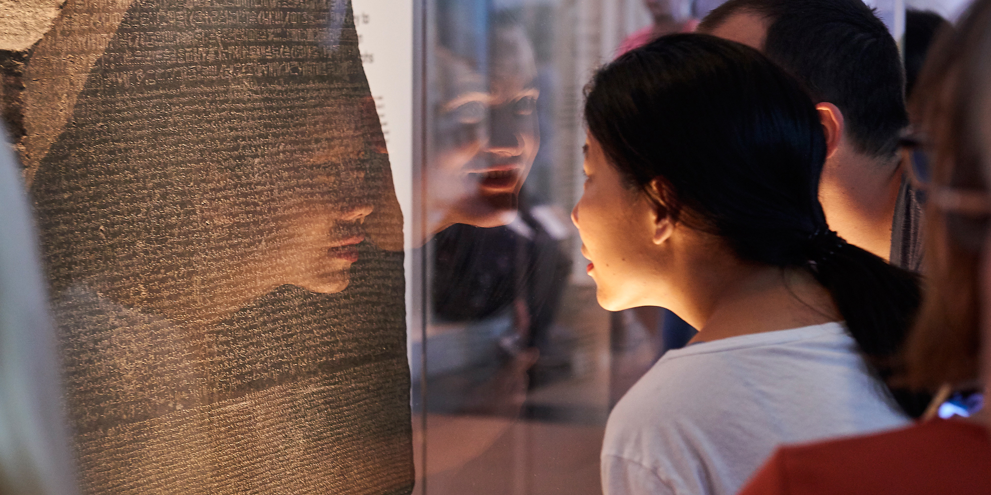 Image of two people looking at the Rosetta Stone in the British Museum