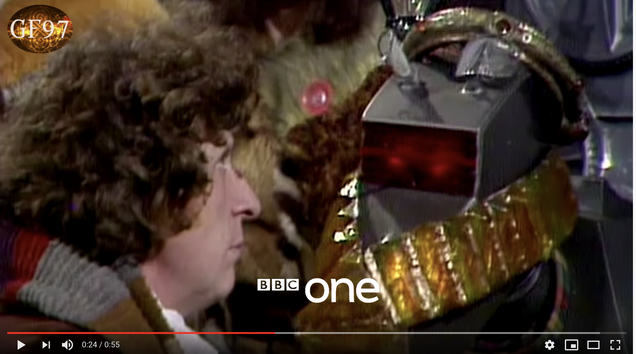 A screen shot from a Dr Who BBC fil showing Tom Baker as the doctor and K9