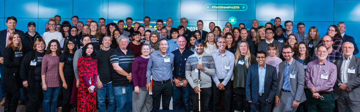 Group shot of attendees at the end of TechShare Pro 2019, standing together on stage smiling at the camera