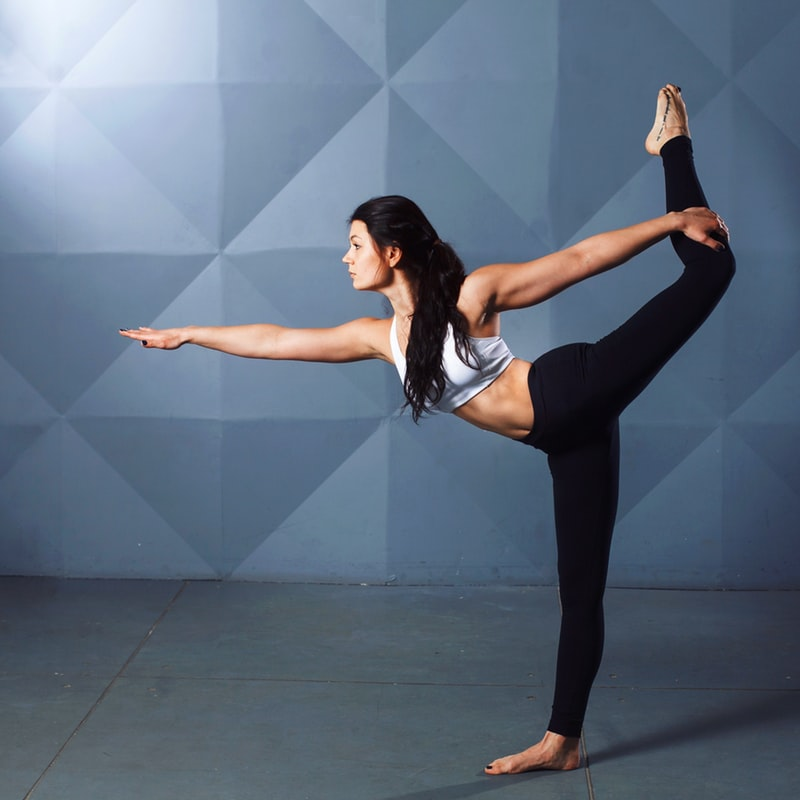 Woman holding a yoga pose on concrete floor
