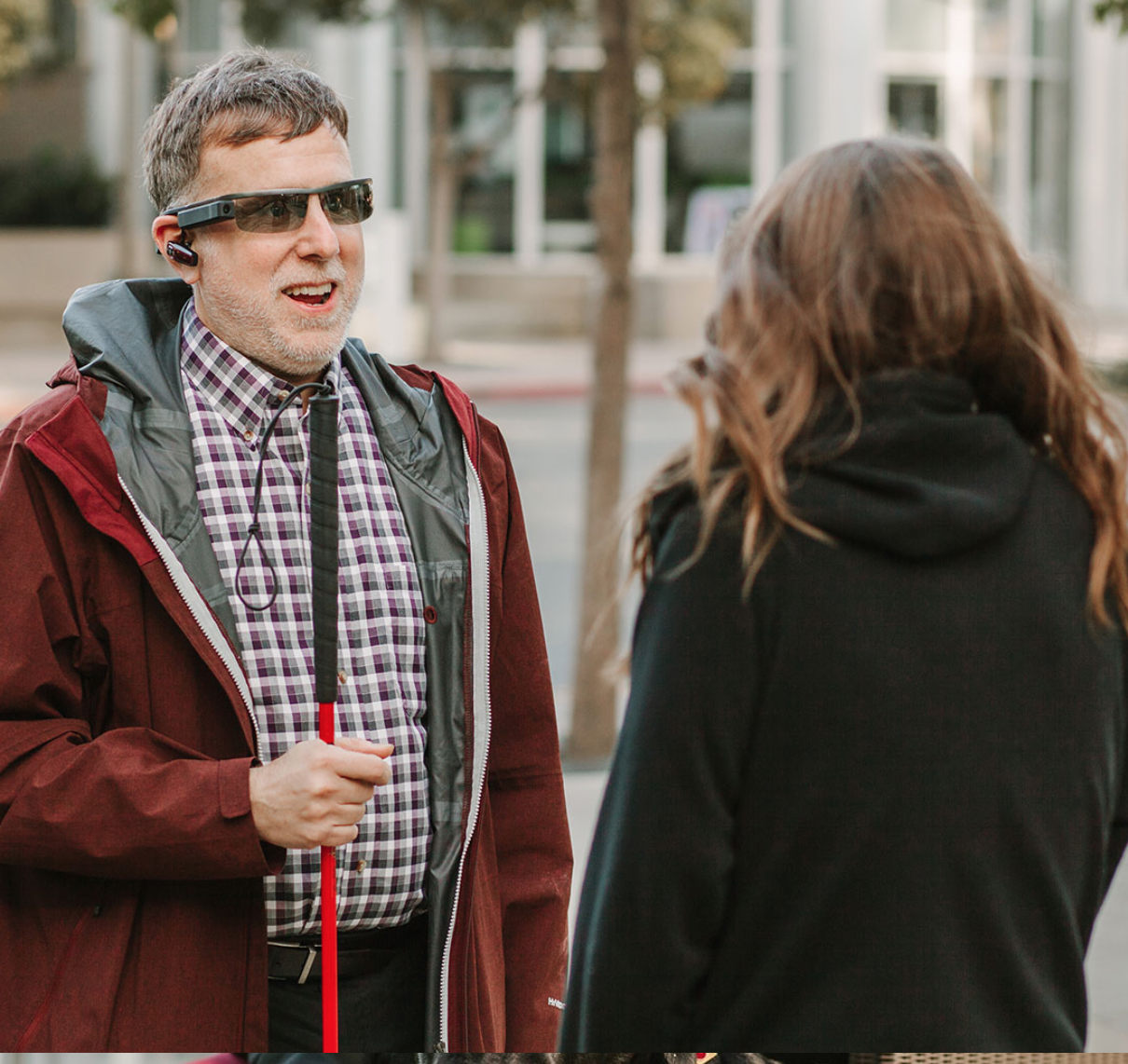Photo of man wearing Aira glasses talking to a woman
