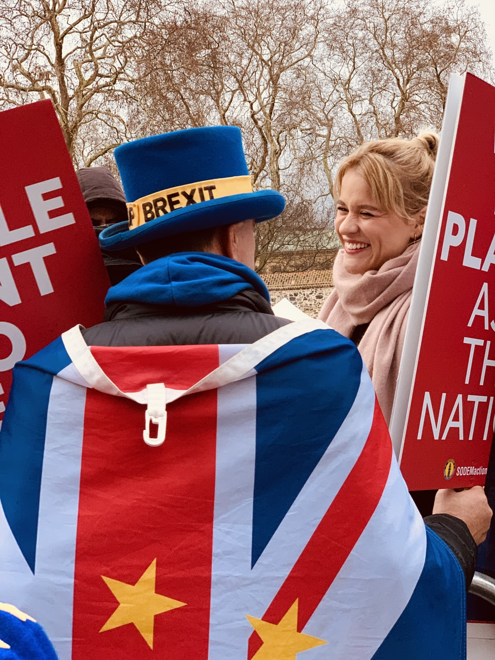 A picture of a man dressed in a top hat with Brexit on it draped in an EU flag. He is holding banners but text cannot be read
