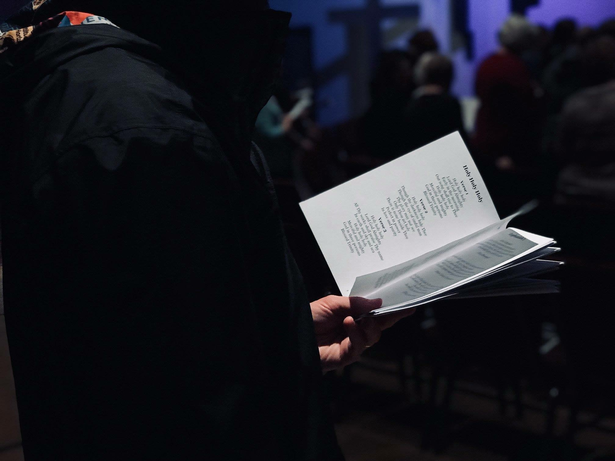 Image shows someones hands holding an order of service