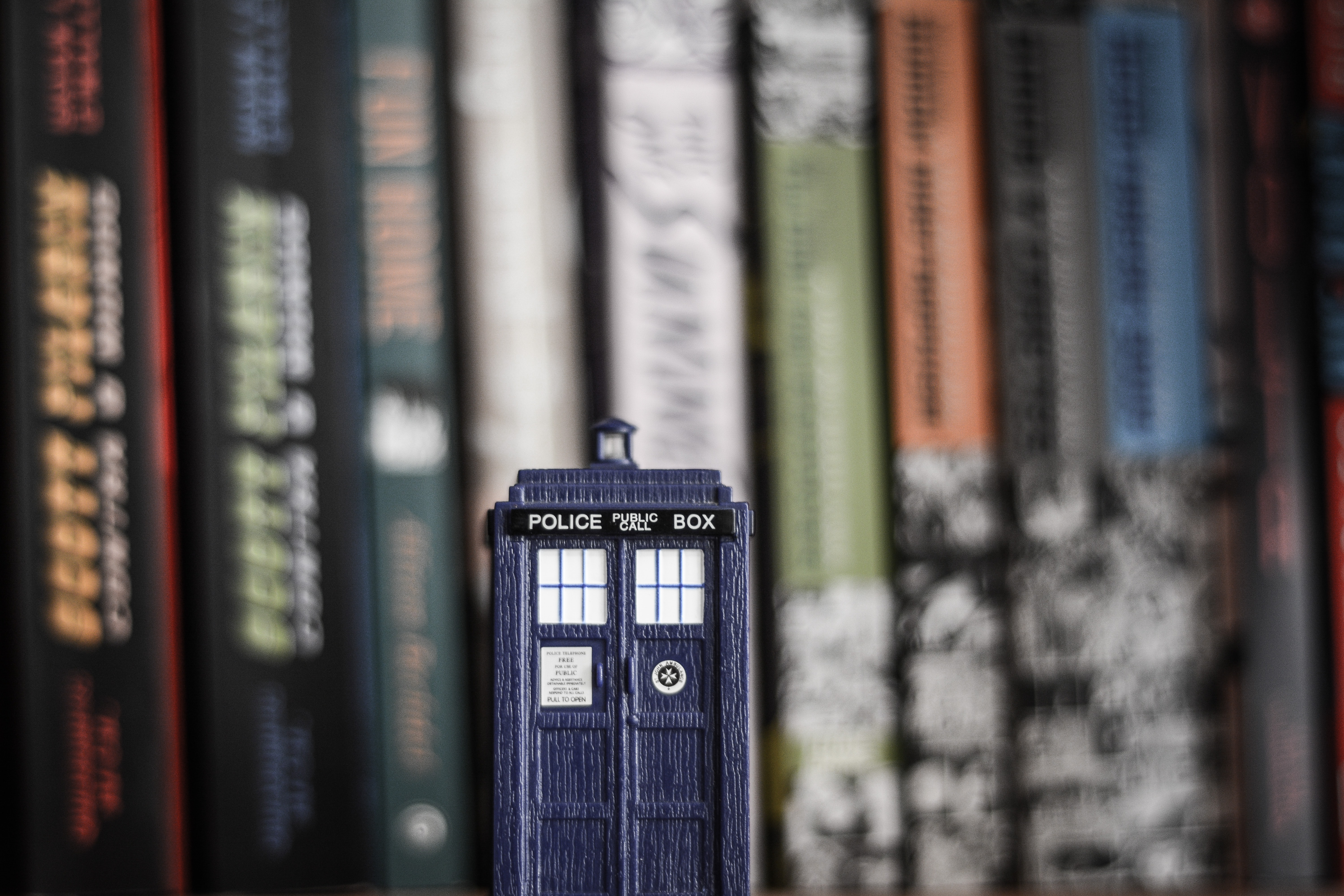 Image shows a small Tardis on a book shelf in front of a row of books