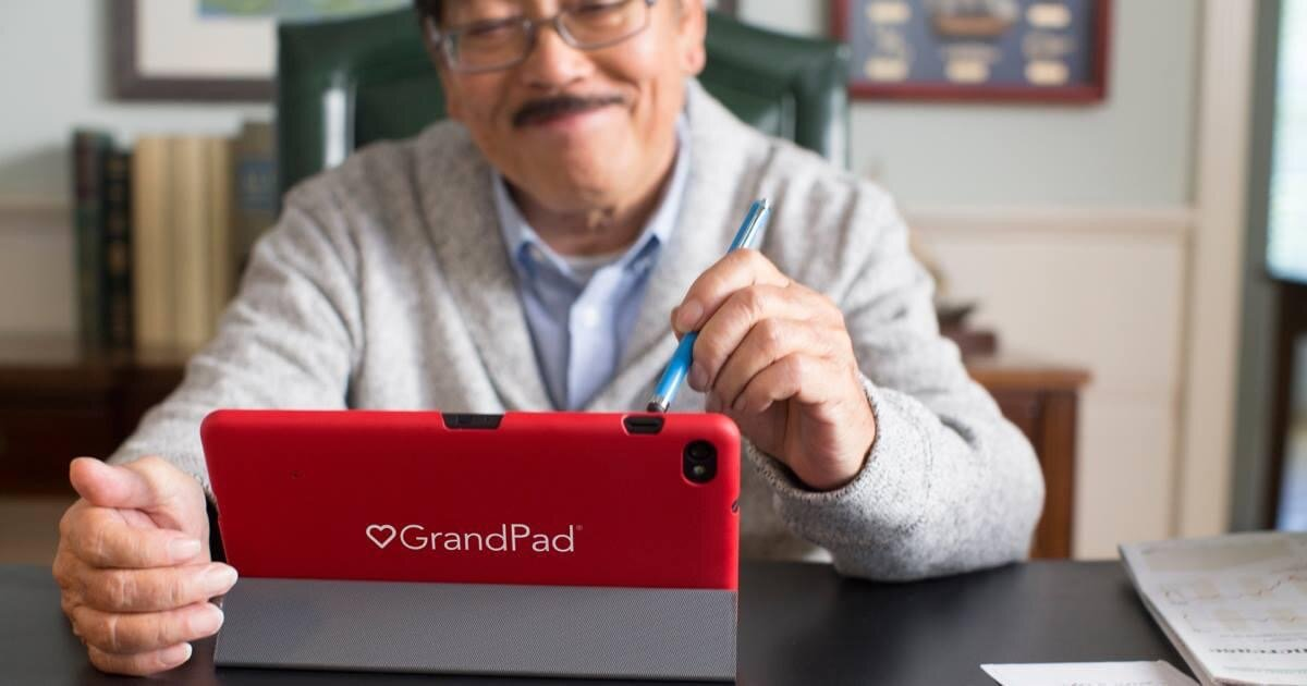 Image shows a man with a moustache looking at a GrandPad device and using it with a stylus-style device