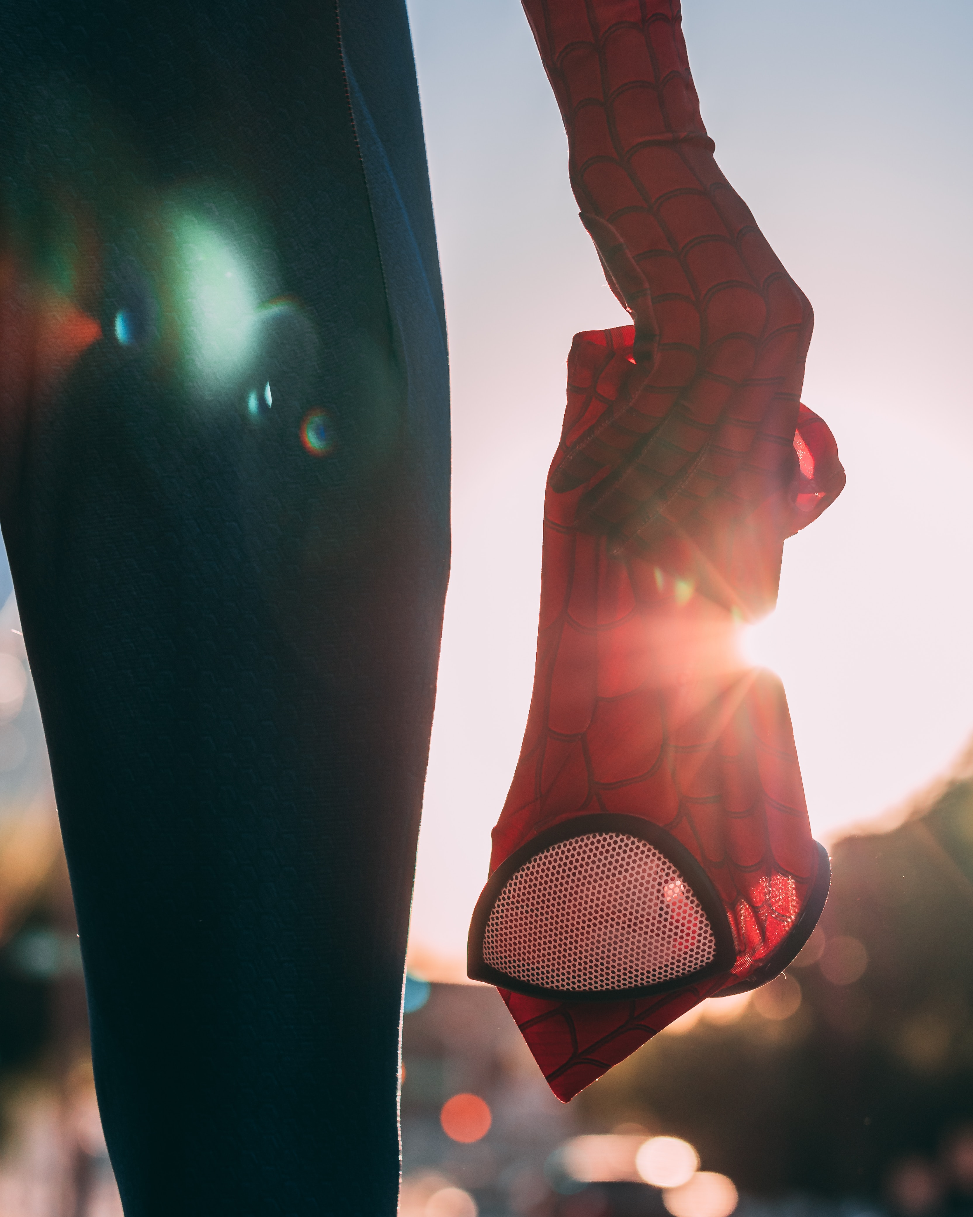 A hand holds what appears to be. superhero mask. Sun shines through.