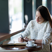 student looking relaxed writing in cafe with hot drink