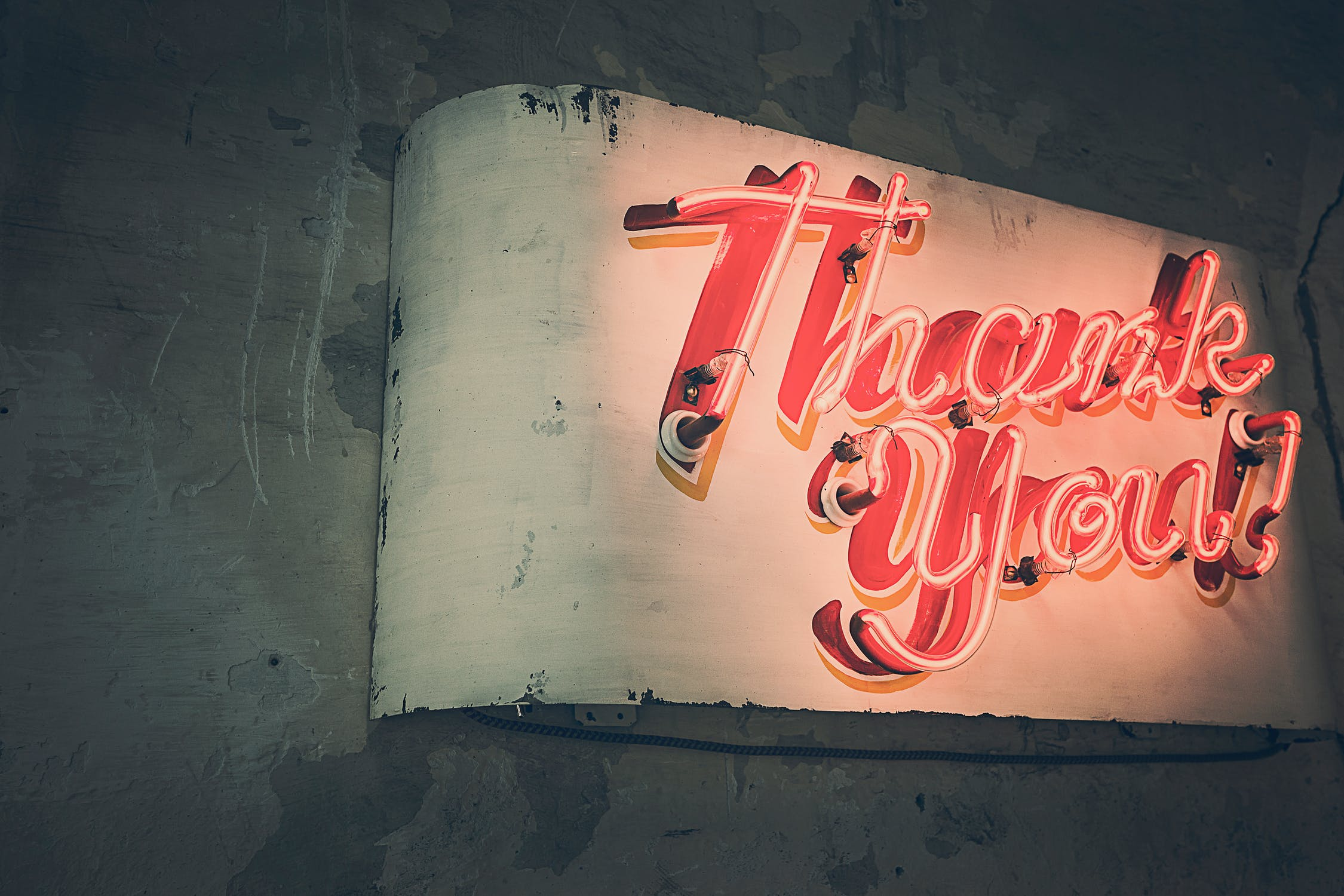 A picture of a neon sign with the words thank you