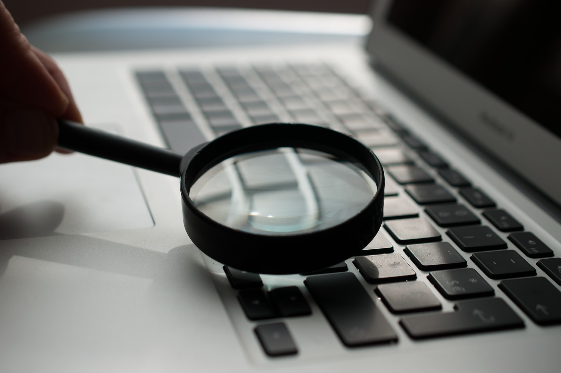 A picture of a magnifying glass over a keyboard