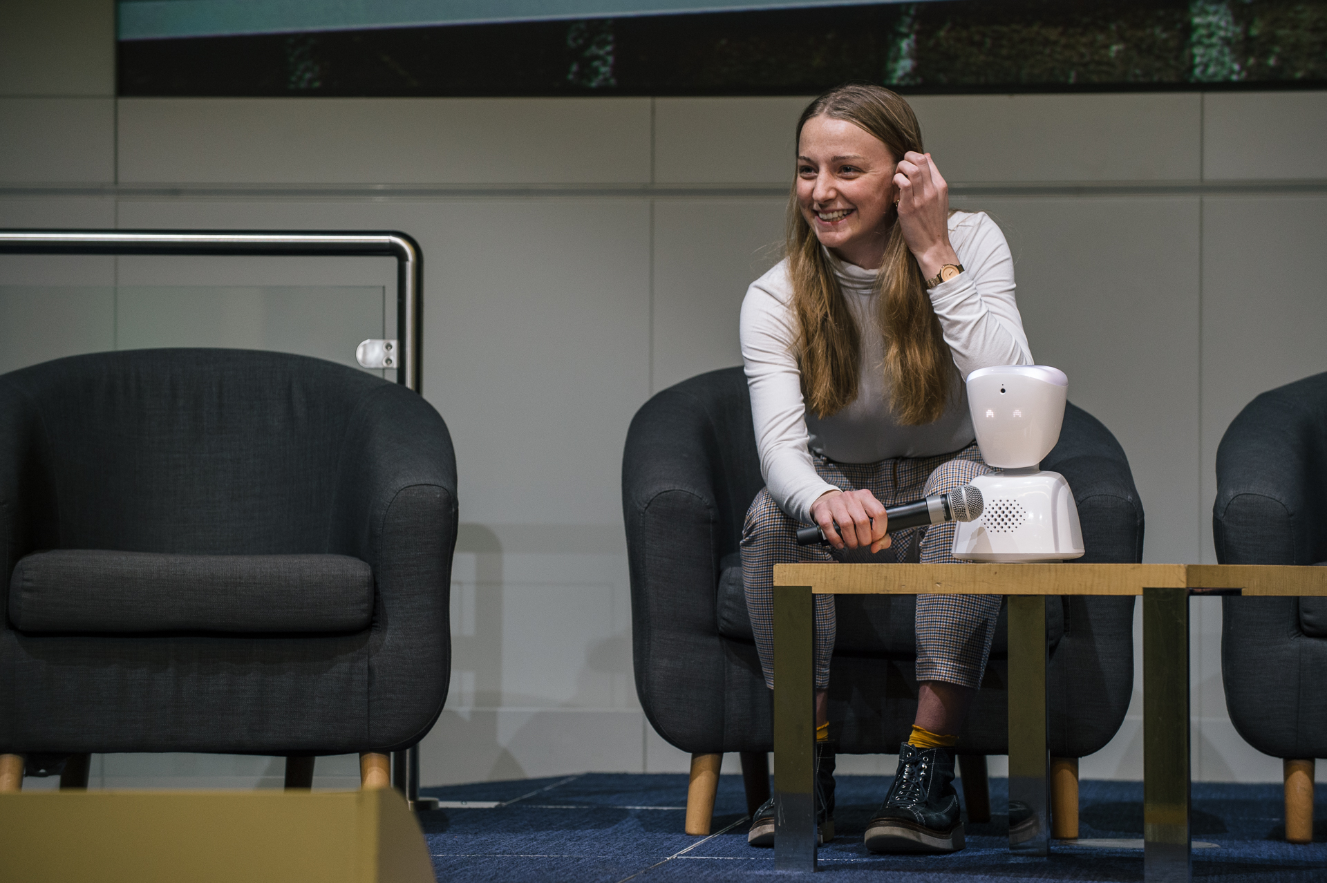 Picture of a smiling girl with the white AV1 robot
