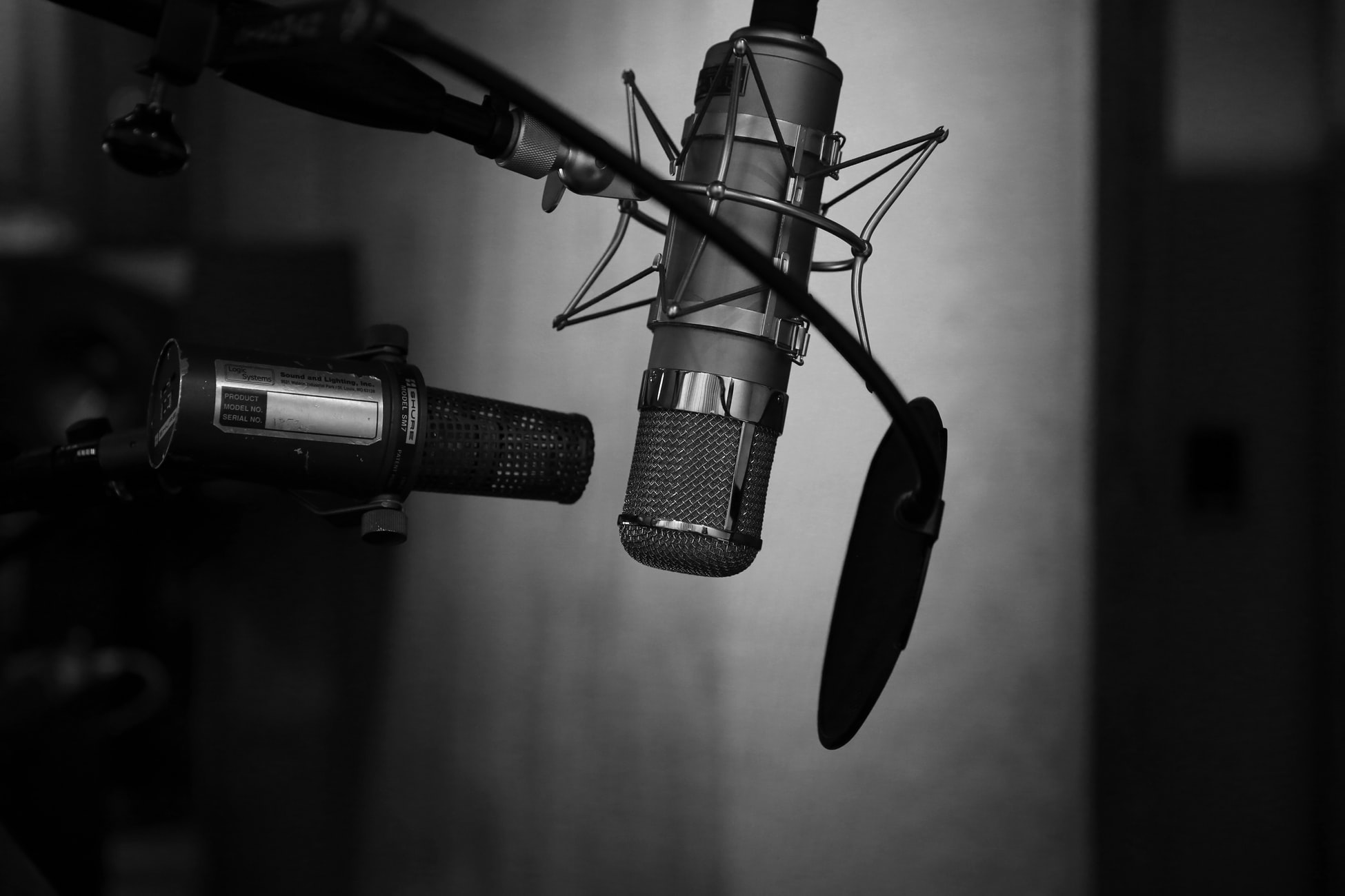 Black and white image shows a microphone in a recording studio