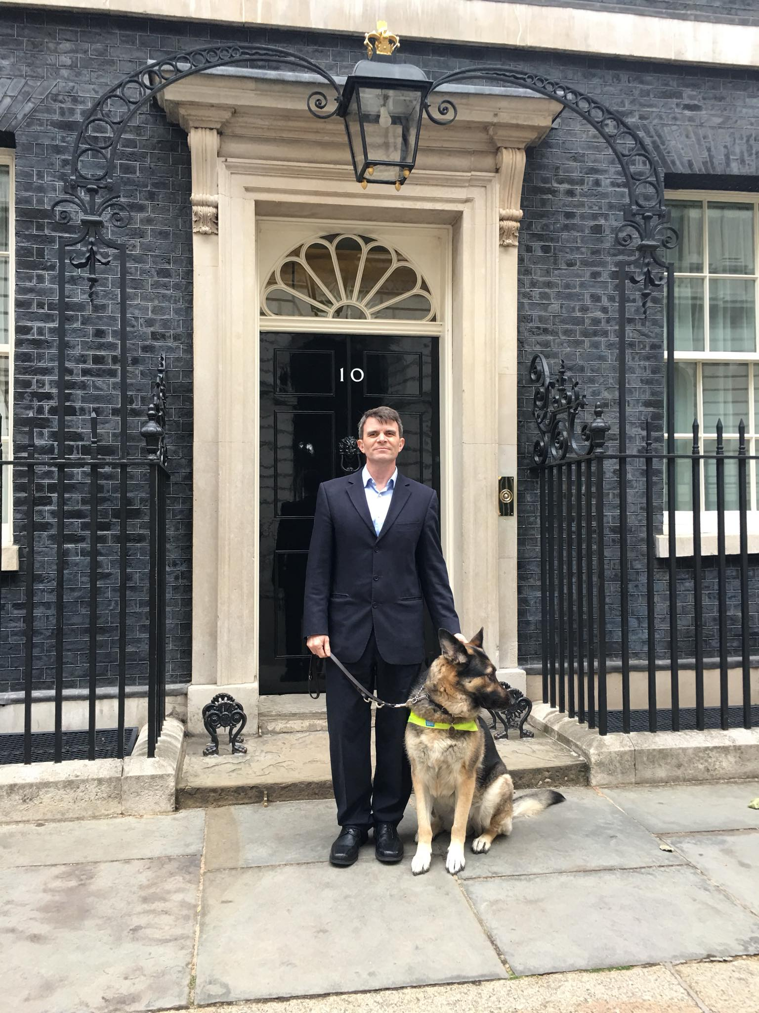 Photo of Robin Christopherson and his dog Archie outside 10 Downing Street