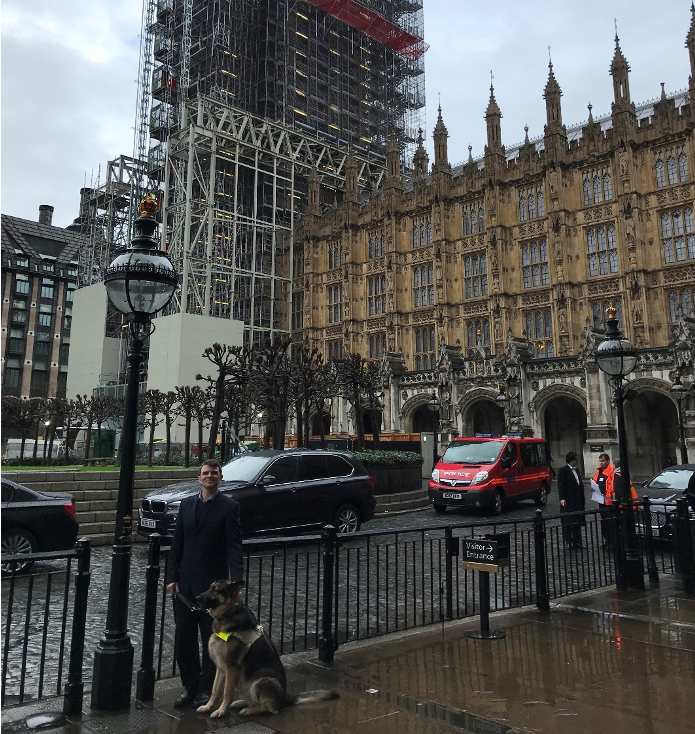 Image of Robin Christopherson and guide dog Archie in front of the Palace of Westminster after giving expert evidence to a government select committee, pre-COVID times