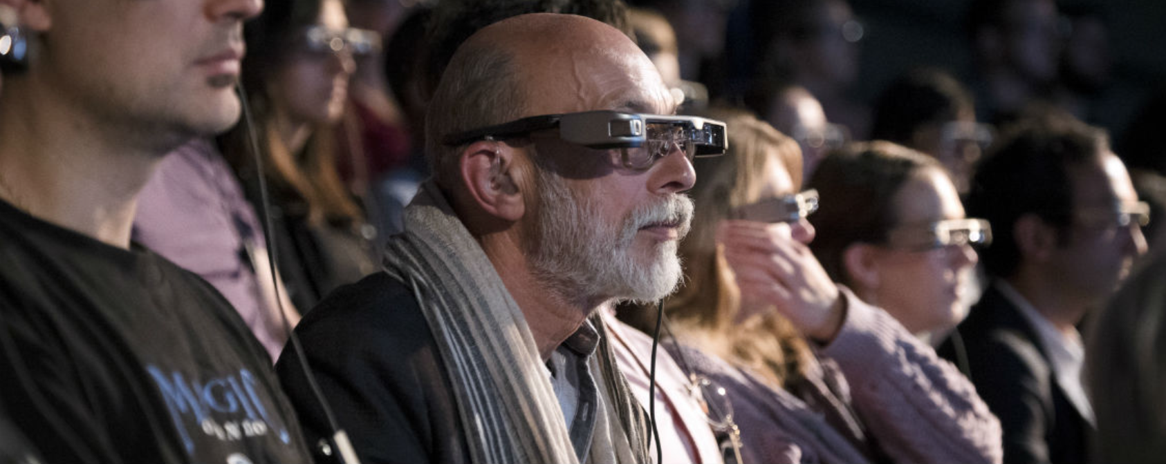 theatre audience wearing smart caption glasses