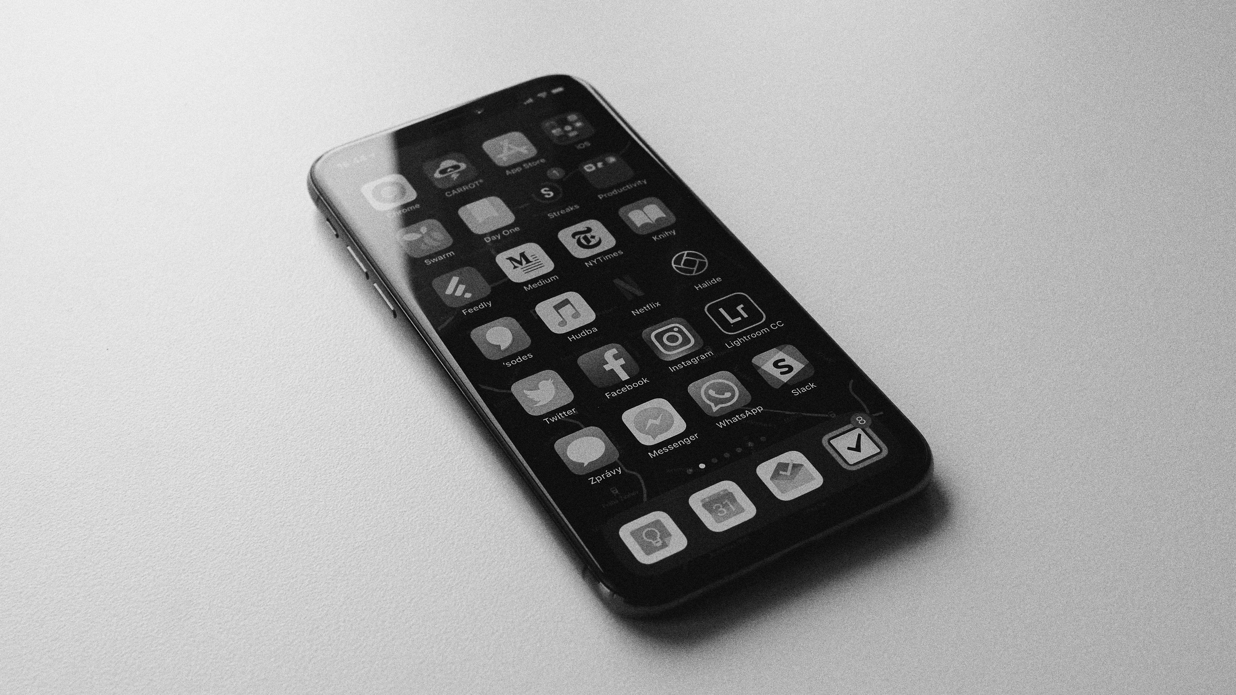 A black and white image of a smartphone with app icons on screen