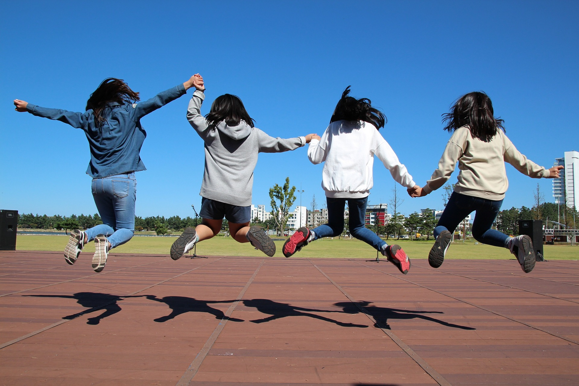 four students jumping in a park