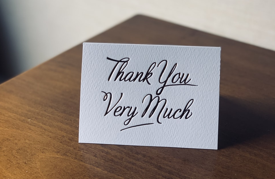 a thank you card sat on a wooden table