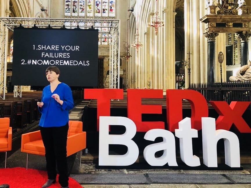A picture of Dr Dominique standing in front of a TEDX Bath sign