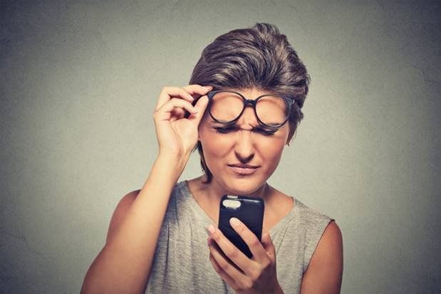 Woman squinting at phone, confused