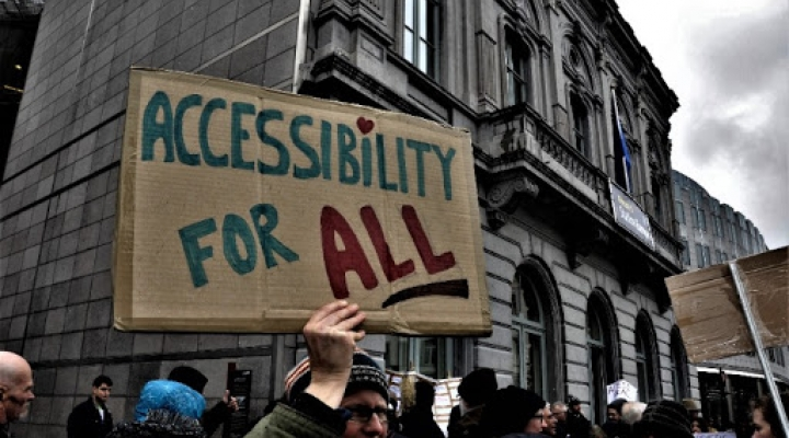 Photo of man in a wheelchair protesting with others holding an Accessibility for All sign