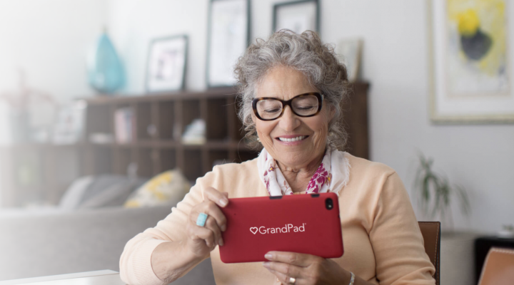 A picture of an older lady cradling the GrandPad tablet. She wears glasses. The tablet is red.