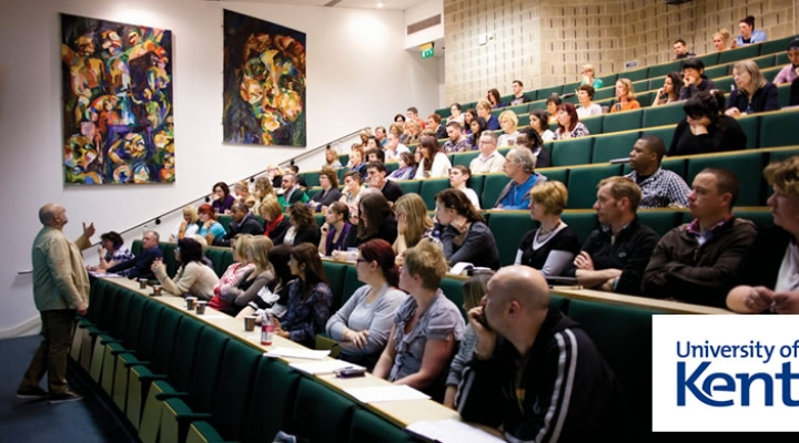 Photograph of a university seminar with students sat in tiered seats and the professor speaking at the front