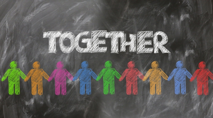 Image shows a blackboard with outline figures in a variety of chalk colours. The people's hands are linked. Text above reads 'Together'.