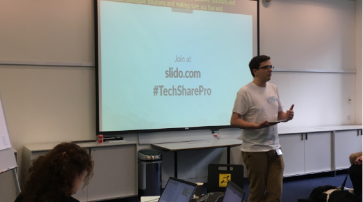 Photo of a man in Techshare Pro breakout room in front of a projector screen inviting audience to join in with Slido