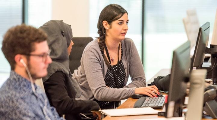 Three people sitting at desks on computer