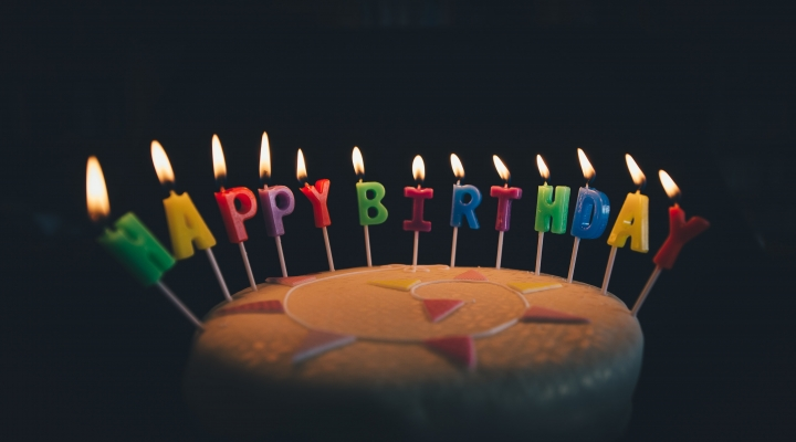 Image shows a birthday cake with candles spelling happy birthday