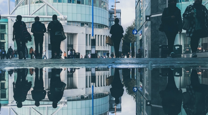 Image shows people against buildings in Birmingham. They are reflected in some water