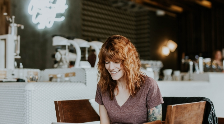 Image shows a girl sitting in a coffee shop smiling while looking at a laptop