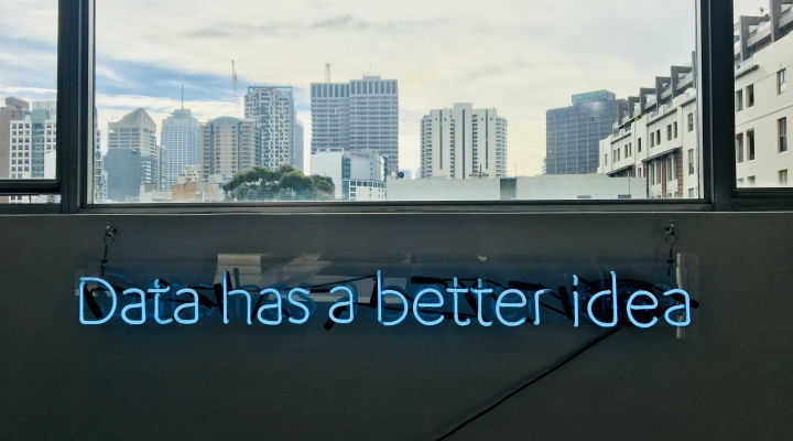 "A neon sign under a window that reads ""data has a better idea"""