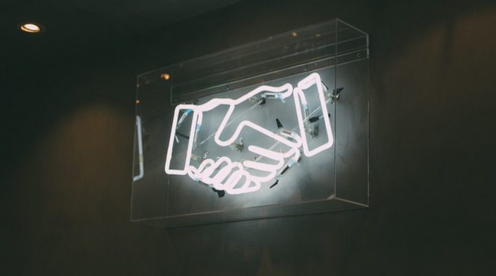 Picture of a neon sign showing the shaking of hands